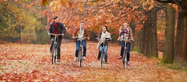 Freunde auf dem Fahrrad im Laub